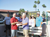 Mike McMillan presents the Canadian Club's check to Marty Eckstein for the purchase of three new scoreboards for the SunBird Shuffleboard Club.