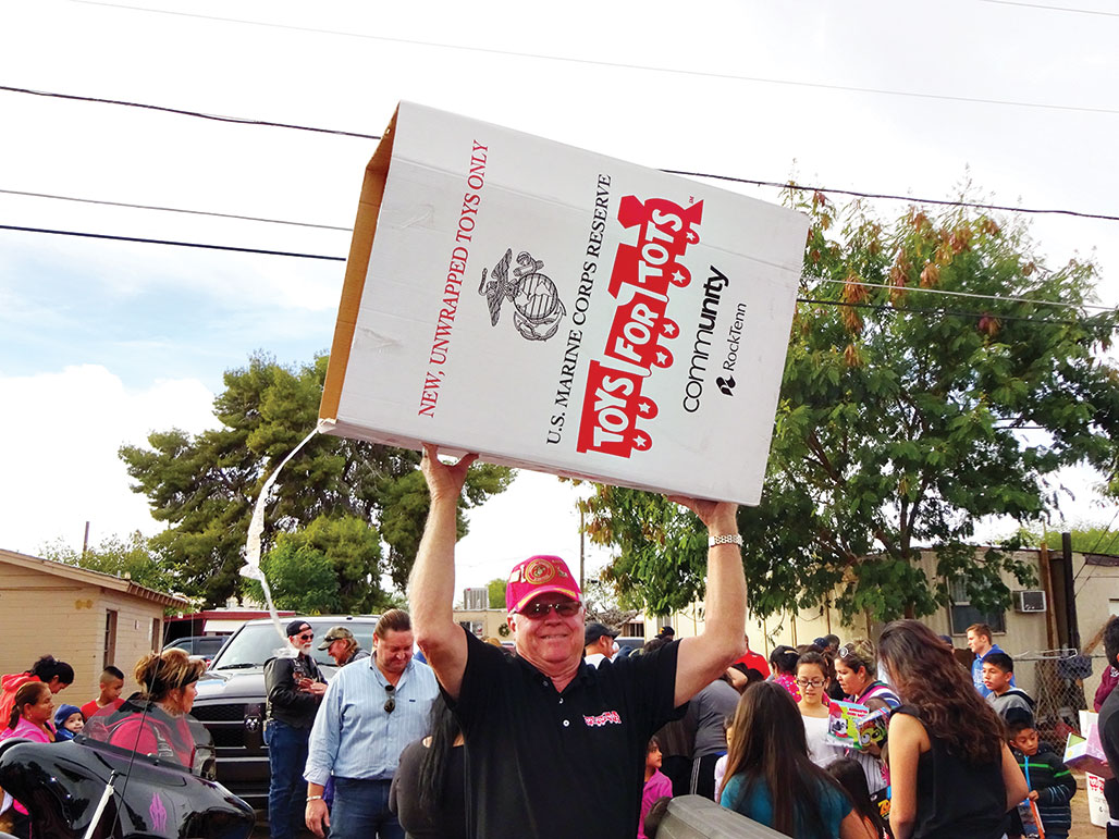John Van Houten, Maricopa County Toys for Tots chairperson for the past five years, carries an emptied toy box back to the delivery truck.