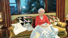 Sue Sossaman displays one of the historic quilts she will talk about at the annual P.E.O. Coffee.