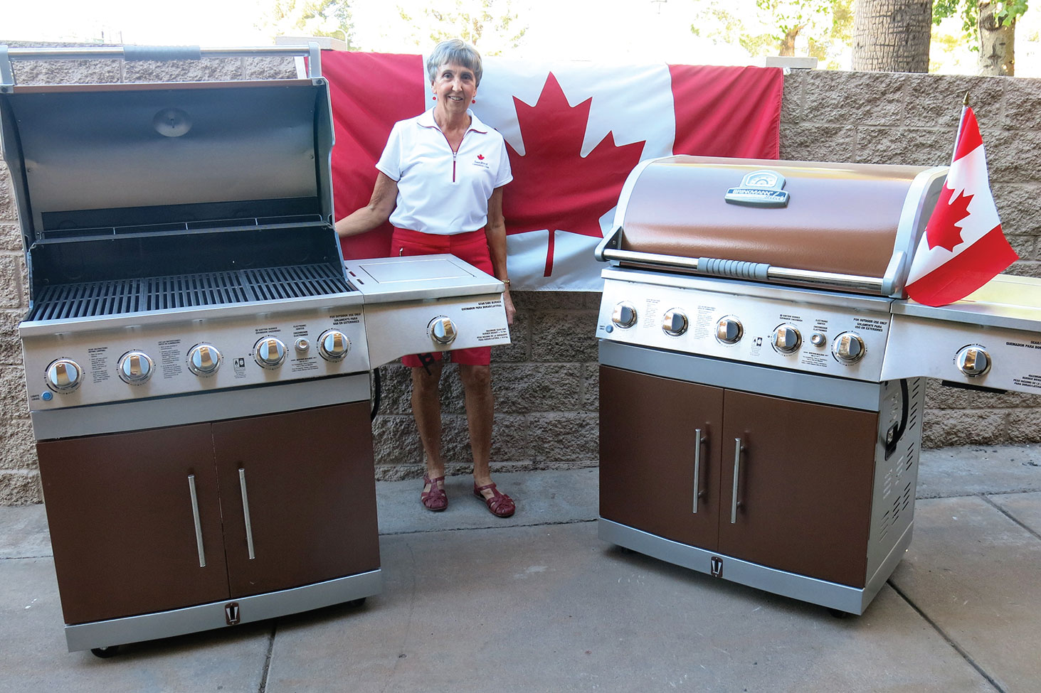 Carolyn Tomlinson proudly displays the two new barbecue grills recently gifted from the Canadian Club to the HOA.