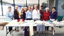SunBird Yarn Club members display their creations before enjoying the spring luncheon.