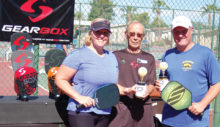 Champions Amy Ricciardi (left) and Matt Ricciardi (right) receiving their trophies from Pete Prucha