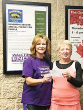 Pam Tiffany, Tennis Club Treasurer, presents a donation of $200 to Marianna Beuscher, President of the Pickleball Club, all for Alzheimer's.