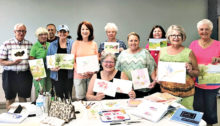 Jean Anderson, seated, with students in her beginning watercolor class display examples of their work.