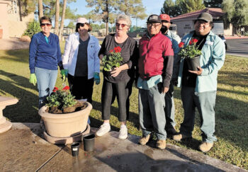 Garden Club members Laurie Doyle, Shelly Seel, and Gudie Huffman with SunBird Golf maintenance crew, planting geraniums by the fountain.