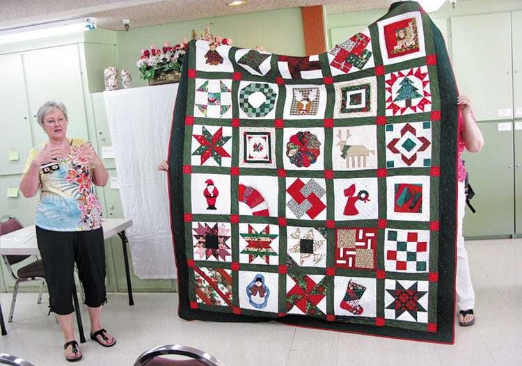 Diana Jones is showing the beautiful quilt that her mother Bobbie Woodward made from a basket of quilt blocks she received from her quilt group at a holiday party in the White Mountains, Show Low area.