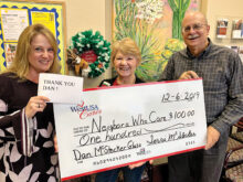 Don McStocker with a $100 check to Neighbors Who Care