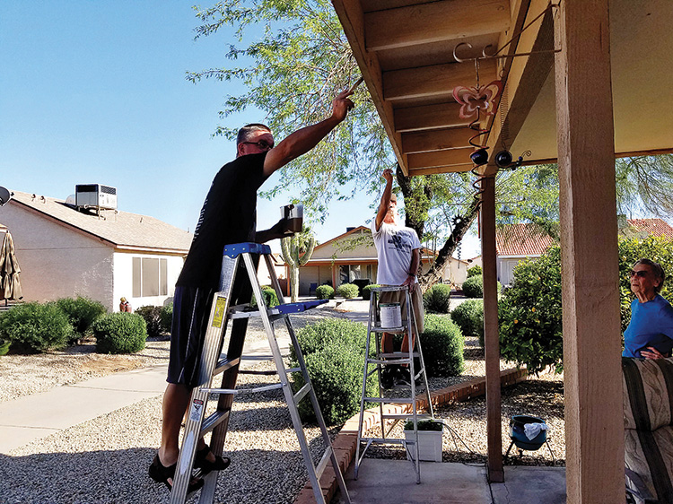 Steve Seel and Bob Bitler paint the trim on an elderly neighbor's home
