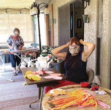 Jacque VanDamme and Pat Seabert work on masks on Jacque's patio. Kathy Bartlett and Kathy Husback also joined in the effort.