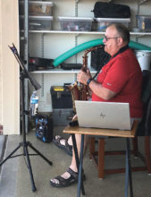 Pat Kelly playing his saxophone from his garage during Five O'Clock Friendly Hour