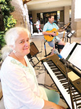 """Kim and Mike Hanson share their musical talent as two of three directors of the SunBird Singers and Ringers. An audience member said, """"I enjoyed this concert more than any I've ever attended!"""" Here they entertain on the patio. They also assist with the SunBird Community Church."""