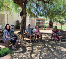 Enjoying the park-like setting are (from left) Alyse and Ryan Birkemeyer with their dogs Archer and Roux, new SunBird homeowners Glenn and Karen Birkemeyer holding granddaughter Aubrey Reinhard, and Kristin and Myles Reinhard. A great meeting place for coffee, to visit, or just enjoy the view!