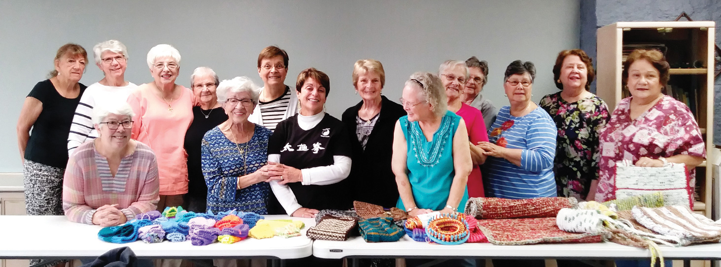 SunBird Knitwits and Bag Ladies show off their creations. This photo was taken in 2019, before the COVID restrictions. In 2021, we all wear masks and maintain social distance.