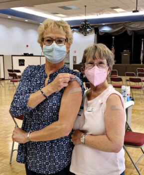 Nurses Karen Volk and Vicki Shay administer COVID vaccines to each other at the SunBird Clinic.